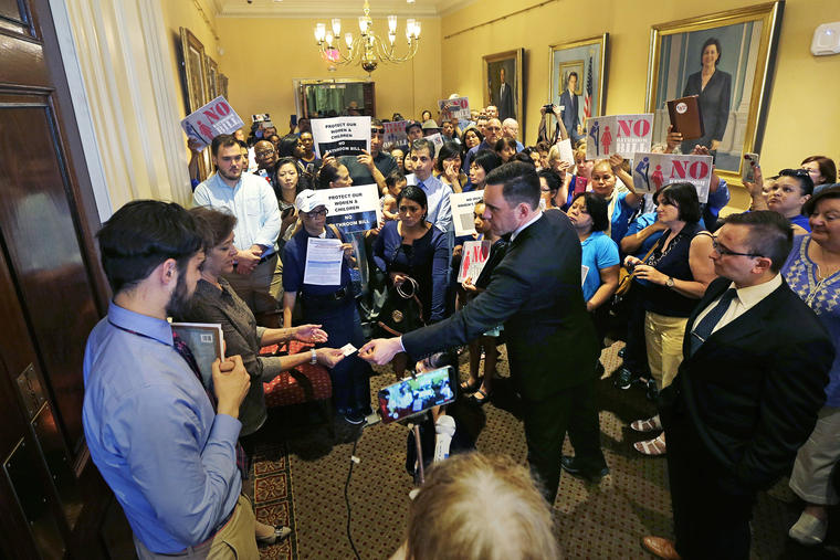 Andrew Beckwith, president of Massachusetts Family Institute, hands his business card to members of Governor Baker's staff, who block the door to his office, as protestors gather at the Statehouse in Boston, Wednesday, June 1, 2016. The Massachusetts House is debating a transgender rights bill that Democratic leaders expect to be passed, and Republican Baker has promised to sign if it reaches his desk. The bill would expand existing protections for transgender people to public accommodations and allow them to use the restroom or locker room that matches their gender identity. (AP Photo/Charles Krupa)